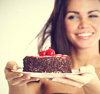 smiling-woman-holding-plate-with-cake 360 195